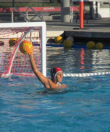 Goalie Andy from boys' water polo searches for an opening to pass the ball to his teammate