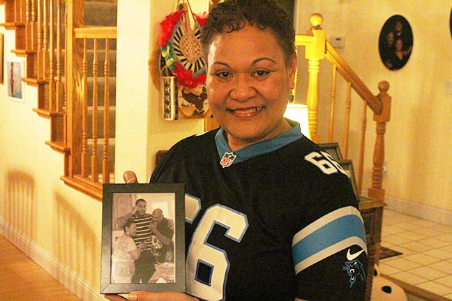 Mrs.+Lupe+Silatolu+holding+a+picture+of+the+moment+Amini+got+the+call+he+was+drafted+into+the+NFL.