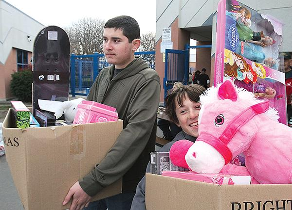 Brothers Josh (left) and Cameron Cortinas wait at the Williams Middle School curb with boxes of toys during the Brighter Christmas distribution Tuesday morning.