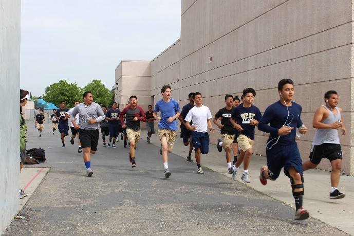 Football conditioning starting their workout with a run