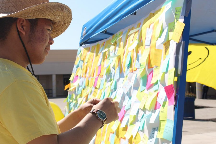 Senior Justin Panopio adds a message to Project Smile's positive board. Photo by Seemani Dash